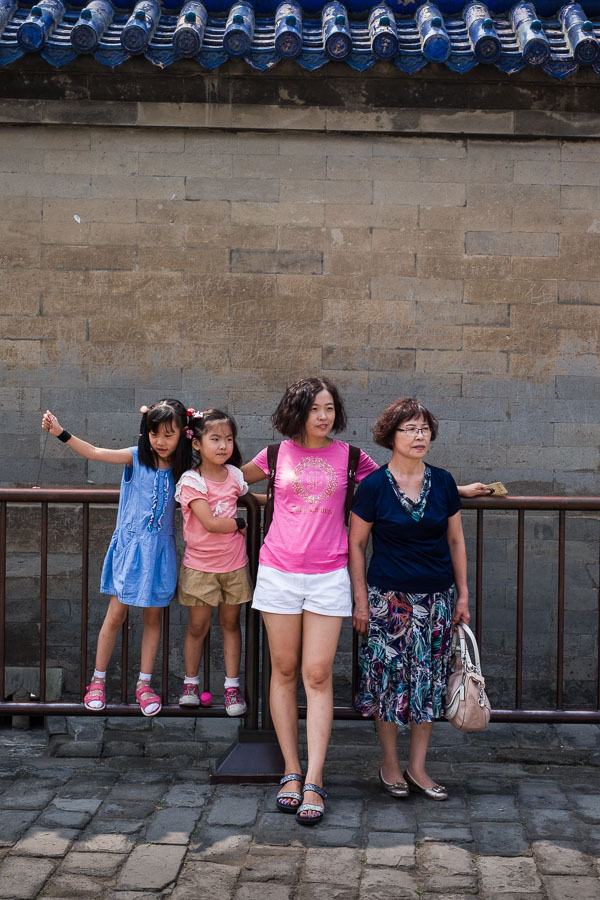Street photo of Chinese family posing for a photo in the Temple of Heaven in Beijing, China
