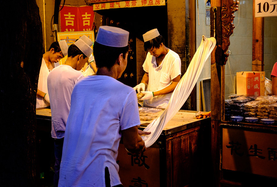Man making noodles at night in market in Muslim quarter of Xi'an China