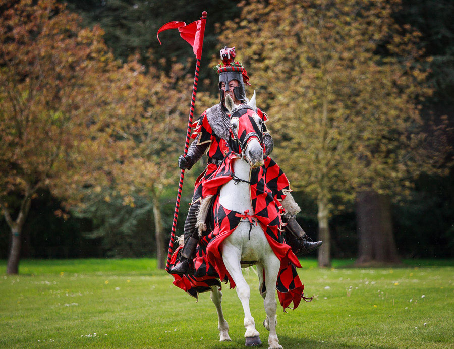 Photo of a knight riding a horse at a jousting tournament taken with a telephoto lens at a wide aperture using phase detection autofocus