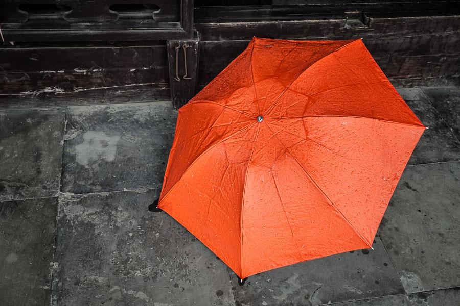 Street photo with orange umbrella
