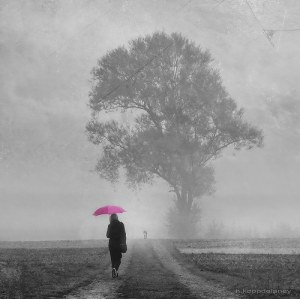 metaphor | a woman walks down a glomy, grey path n the distance, but holds a bright pink umbrella above her - an indication of brighter things to come.