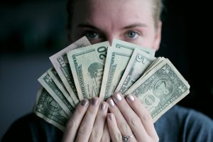Woman holding money in front of her face by Sharon McCutcheon