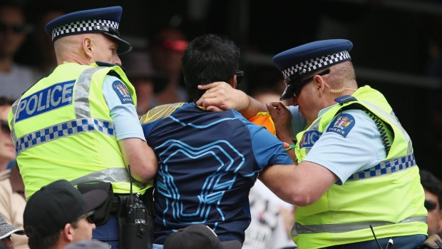 A Sri Lankan fan is removed from the Eden Park stands by police.