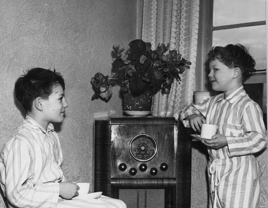 Richard (left) and John Hutton, sons of English cricketer Sir Leonard Hutton, wearing pyjamas at home at Leeds. They are listening to a broadcast of a test match in Australia in which their father is playing. Image Courtesy: Getty Images