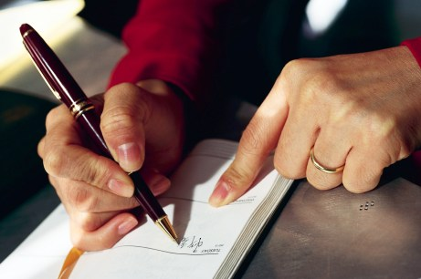 Woman Writing in Daily Planner