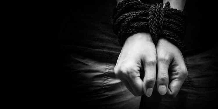 Human trafficking. Hands bound together,