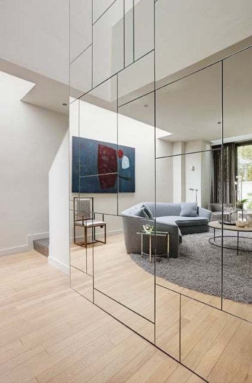 geometric-mirrored-wall-conceals-closets-and-storage-spaces