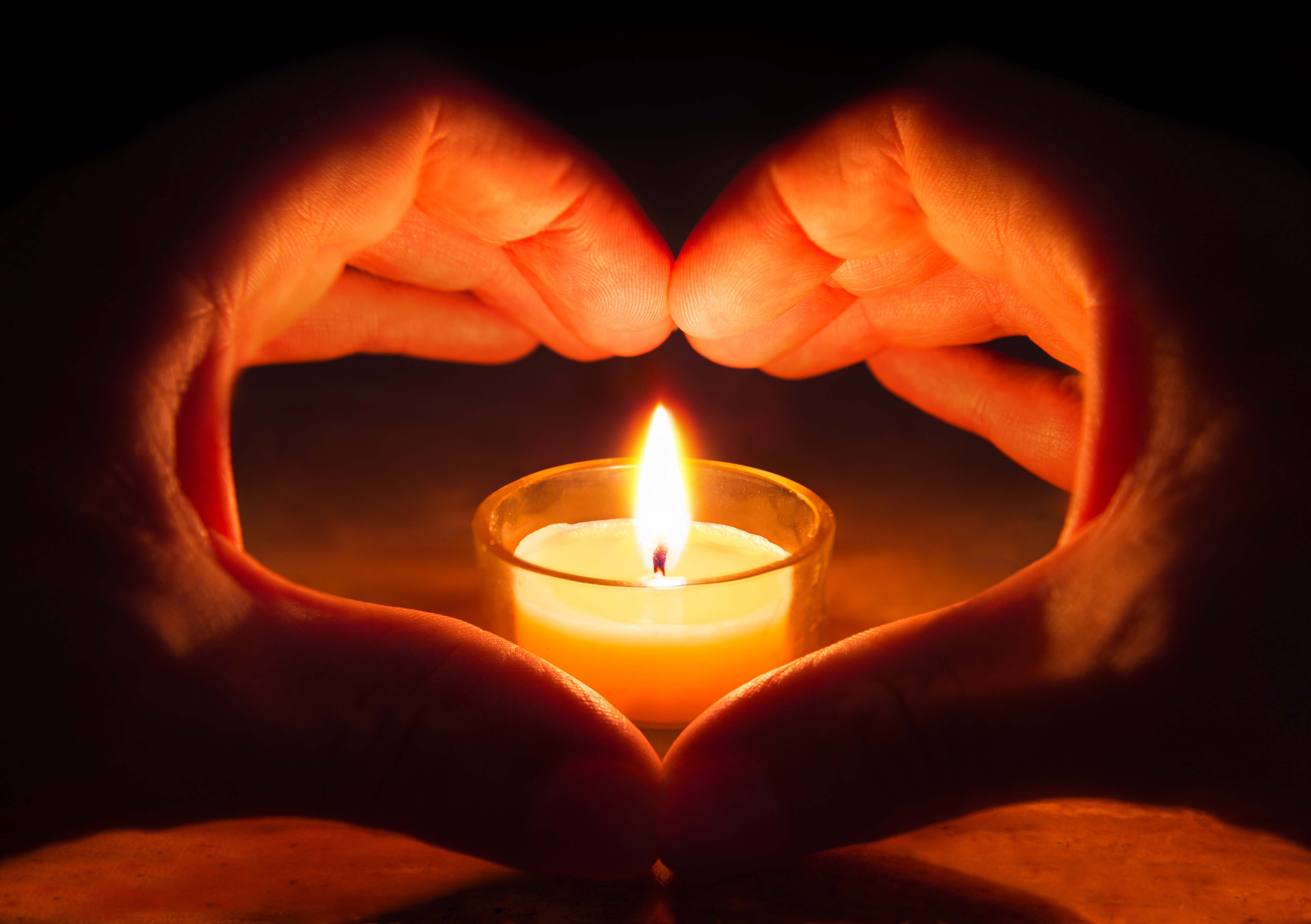 Hands forming heart around a candle