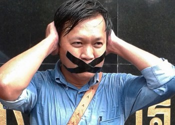 """Pravit Rojanaphruk, an outspoken Thai columnist for the English-language daily The Nation, poses for  photograph while being called to report himself to the ruling military along with other journalists in Bangkok, Thailand Sunday, May 25, 2014. A spokesman for Thailand's coup leaders said Sunday that democracy had caused """"losses"""" for the country, as the junta sought to combat growing international condemnation and hundreds of protesters angrily confronted soldiers in central Bangkok. (AP Photo)"""