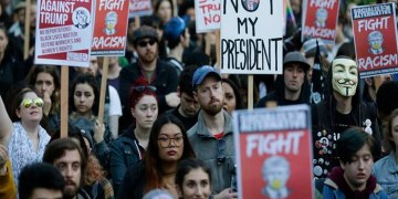 People hold signs as they listen to speakers at a protest against the election of President-elect Donald Trump, Wednesday, Nov. 9, 2016, in downtown Seattle. (AP Photo/Ted S. Warren)