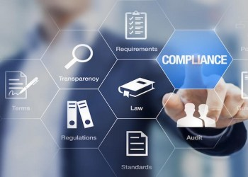 Compliance concept with icons for regulations, law, standards, requirements and audit on a virtual screen with a business person touching a button