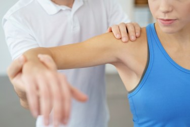 Image of physical therapist examining patient