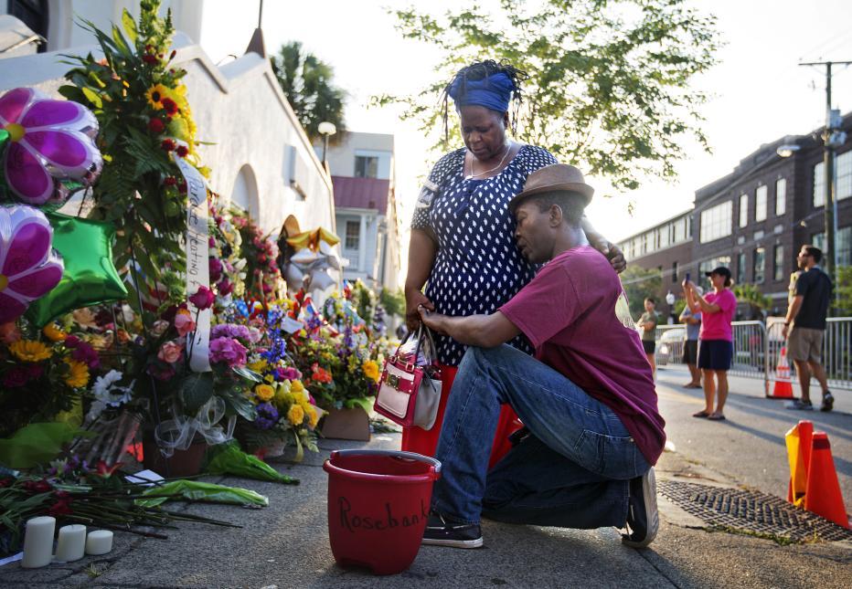 2015. Iglesia en Charleston, Carolina del Sur. Dylann Roof, un supremacista blanco de 19 años, entró a una lectura de la Biblia en una iglesia de una comunidad afroamericana en la que participaban varios feligreses. Luego de una hora en la reunión sacó su arma y asesinó a nueve personas. Fue arrestado al día siguiente del ataque y condenado a muerte por asesinatos y crímenes de odio. En la fotografía, los miembros de la comunidad donde ocurrió el incidente, Allen Sanders y su esposa Georgette, rezan frente a la iglesia después de la matanza. 17 de junio de 2015.