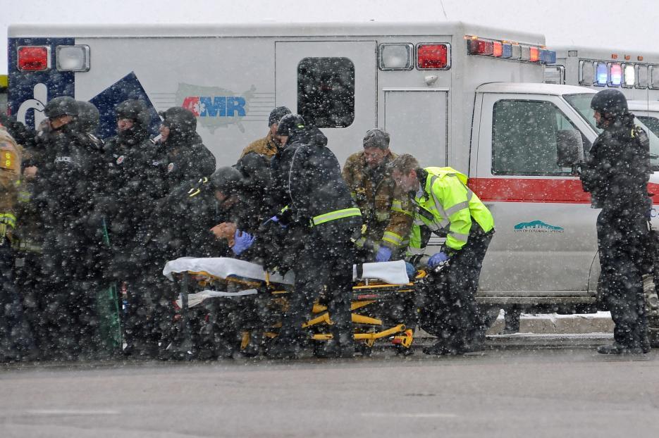 2015. Clínica de planificación familiar en Colorado Springs, Colorado. Robert Lewis Dear, de 60 años de edad, atacó con un arma larga una clínica de planificación familiar de Planned Parenthood, una organización que ofrece salud reproductiva. Asesinó a tres personas, dos civiles y un policía. Luego de varias horas de enfrentamiento con la policía fue arrestado. En la fotografía uno de los policías heridos en el enfrentamiento es asistido por los servicios de emergencia. 27 de noviembre de 2015.