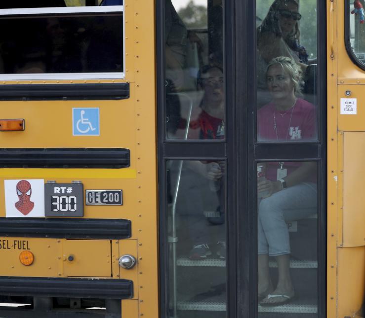 Personal de la escuela esperando para ser trasladados en autobuses escolares.