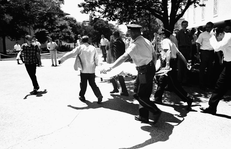 1966. Universidad de Texas, en Austin, Texas. Este fue el primer tiroteo masivo en un centro educativo de EEUU. Charles Whitman, un exmarine de 25 años y estudiante de la Universidad de Texas que padecía de ataques de ira disparó desde una torre del campus como francotirador. Mató a 17 personas y dejó a 31 heridos entre estudiantes y empleados de la universidad. Había asesinado a su esposa y a su madre la noche anterior. Fue abatido por la policía en la torre desde donde disparaba. En la fotografía, una de las víctimas de Whitman cuando era asistida por las autoridades. 1 de agosto de 1966.