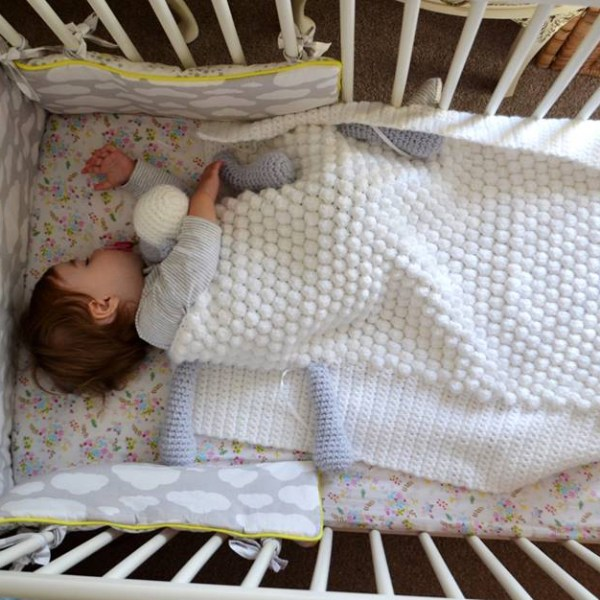 Baby covered with crochet sheep baby blanket in a cot
