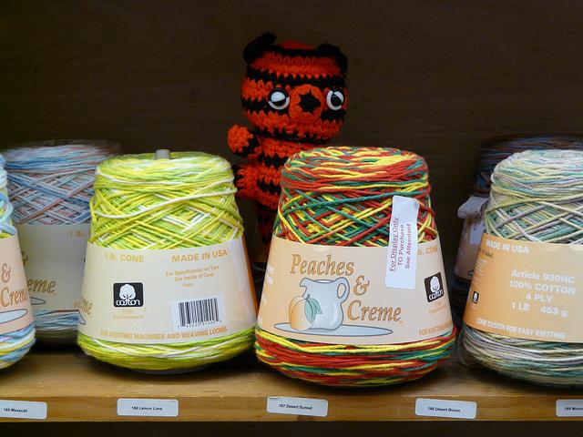crochet tiger behind cones of cotton yarn