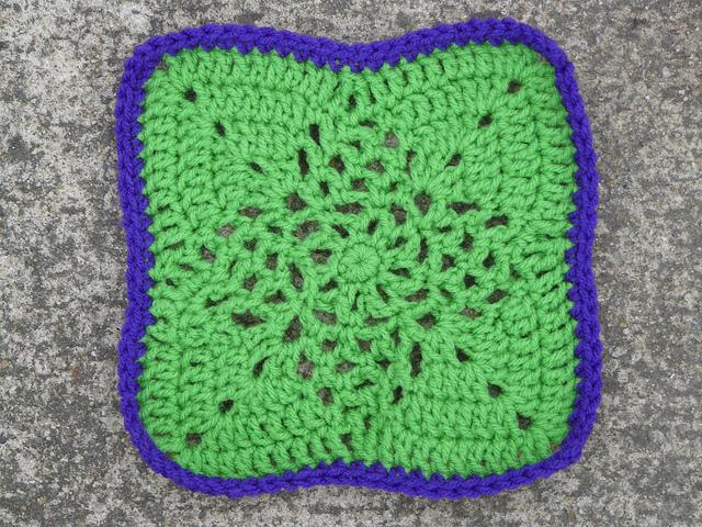 Green crochet square with purple edge