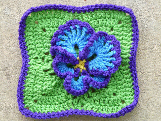 Crochet granny square with a pansy appliqué