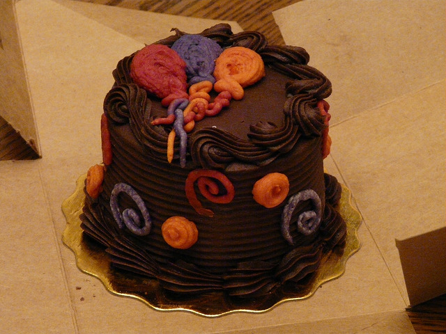 chocolate cake with orange, purple, and red balloons
