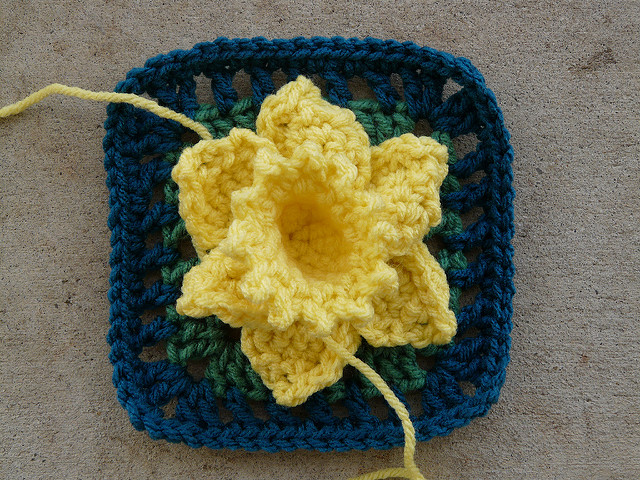A crochet daffodil to be appliqued onto a crochet square