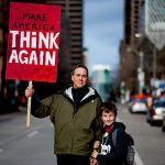Padre e hijo sosteniendo una pancarta