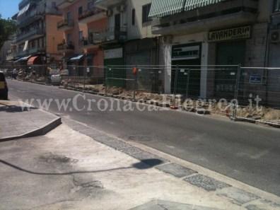 Le facciate delle attività commerciali coperti da reti metalliche del cantiere di lavoro in via Campi Flegrei, ad Arcofelice