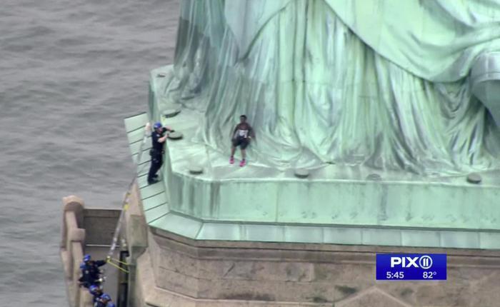 """New York, donna sulla Statua della Libertà: protesta contro Trump: """"Libera tutti i bambini"""""""