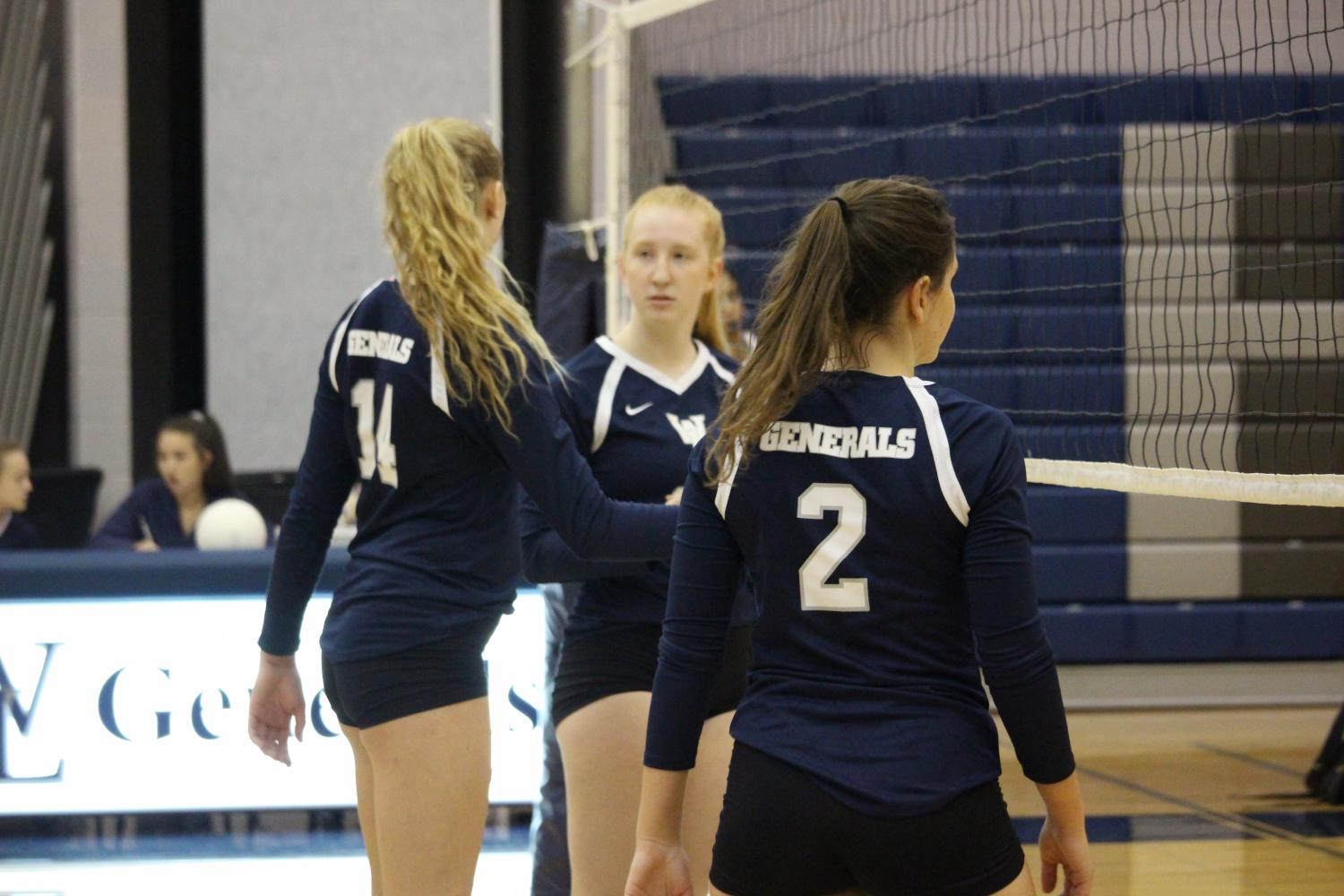Varsity volleyball players Genevieve Bernard, Kate Sheire and Hannah Demas stand at the net in between plays.