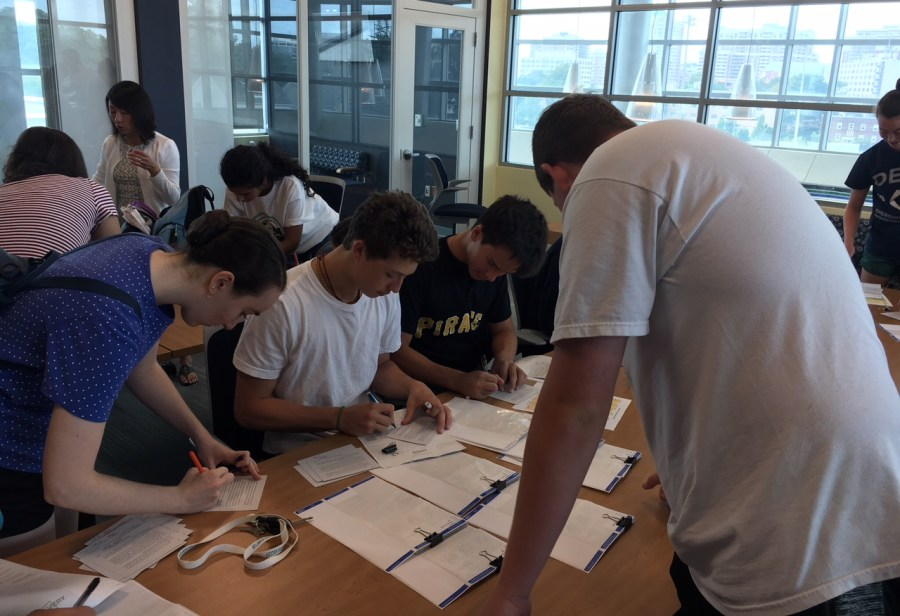 Juniors+Julia+Timpane+and+Angelo+Lepore+and+senior+Matthew+Hopper+sign+postcards+for+the+incoming+freshmen.+Every+year+the+mentors+mail+out+a+card+with+a+short+letter+about+the+Connect+Mentors+Program+for+each+freshman.