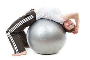 Woman stretching her back by leaning backwards into a big ball