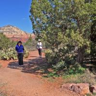 2 women walking in a focused way on red rock trail practicing nature connection