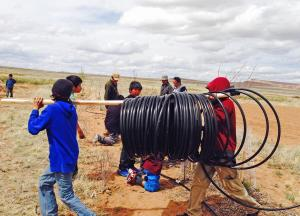 Hopi youth farming group laying out drip system pipe.