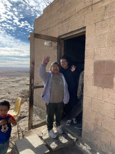 Hopi family waving from open door of cliff edge home.