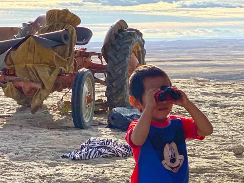 Hopi boy with new binoculars on top of cliff edge with tractor in background represents Hopi youth looking to the future and welcoming learning enrichment supplies and vision for the future
