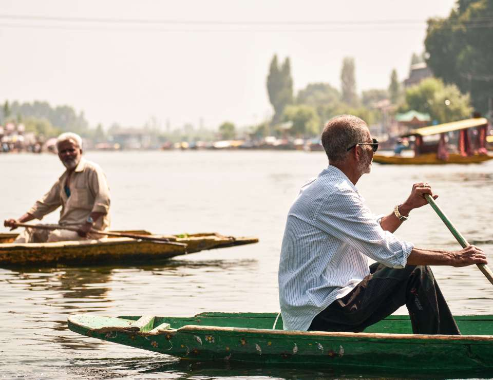 people crossing each other while boating at the dal lake
