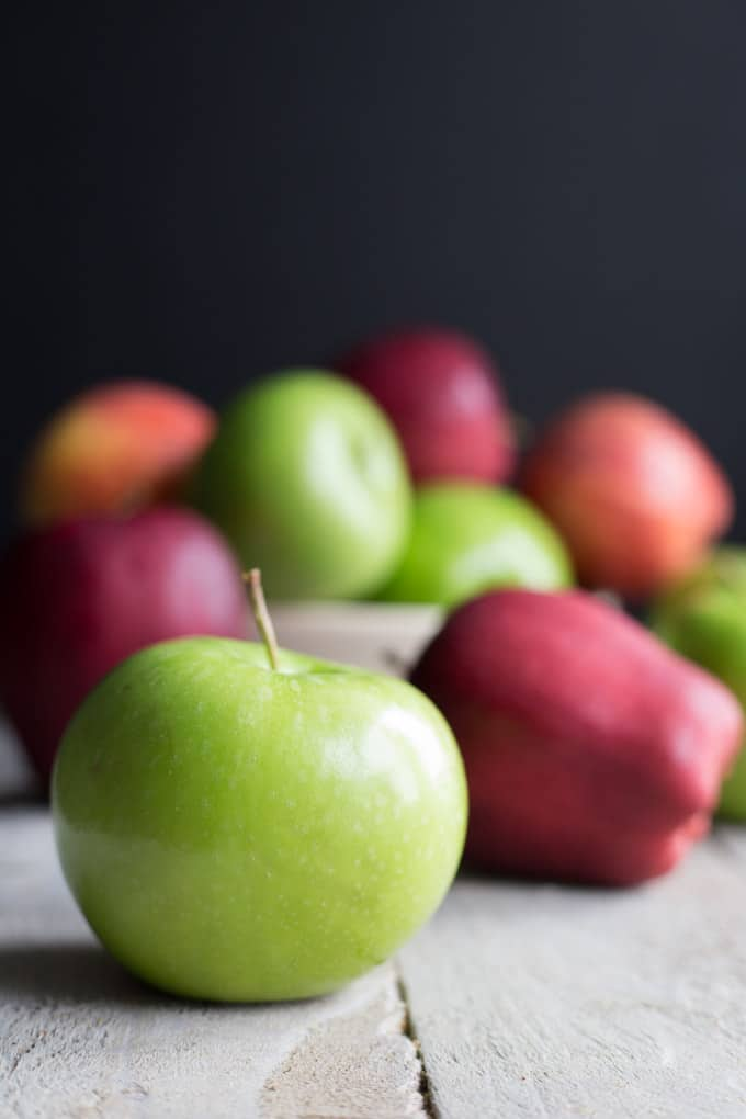 Red and green apples arranged on a wooden surface.
