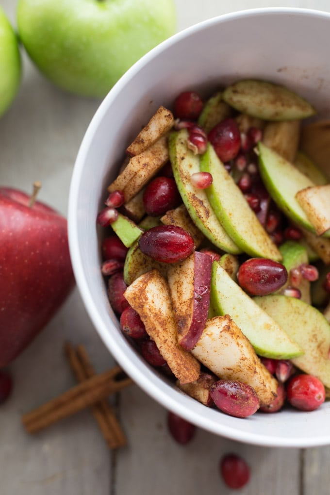 Overhead view of sliced apples, cranberries and pomegranate arils in a white bowl.