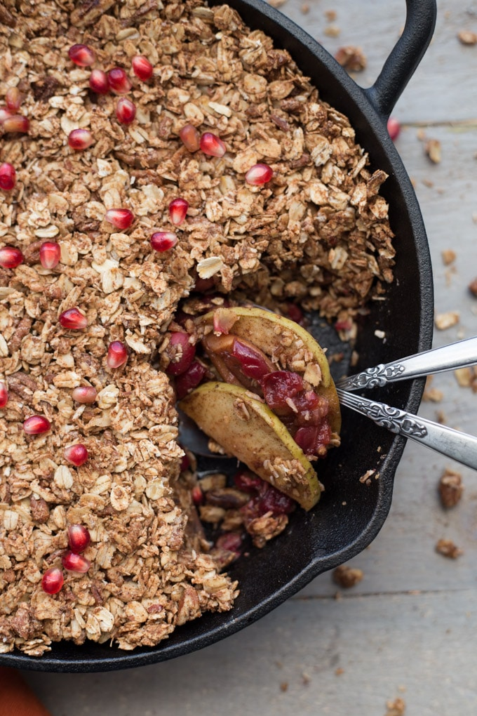 Apple, Cranberry and Pomegranate Oatmeal Crisp in a black cast iron pan.