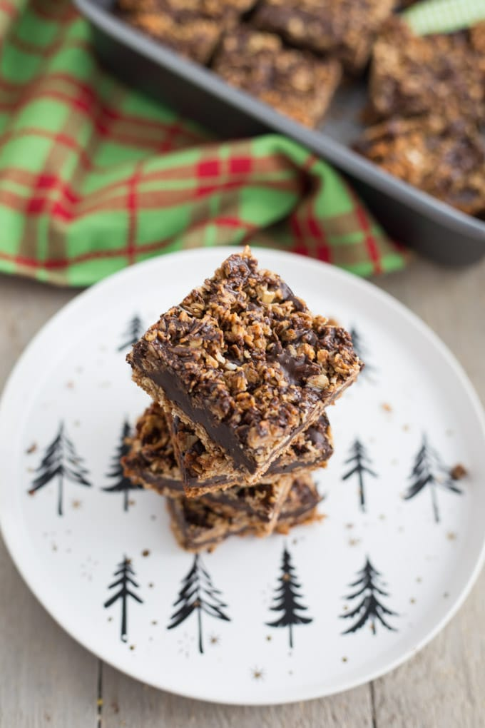 Overhead view of a stack of Chocolate Chai Spice Crumble Bars on a Christmas plate with pan of bars in background.