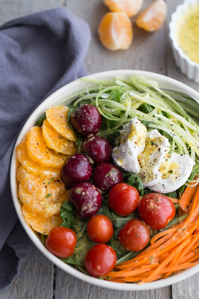 Winter Sunshine Salad with Citrus Honey Dressing in a white bowl.