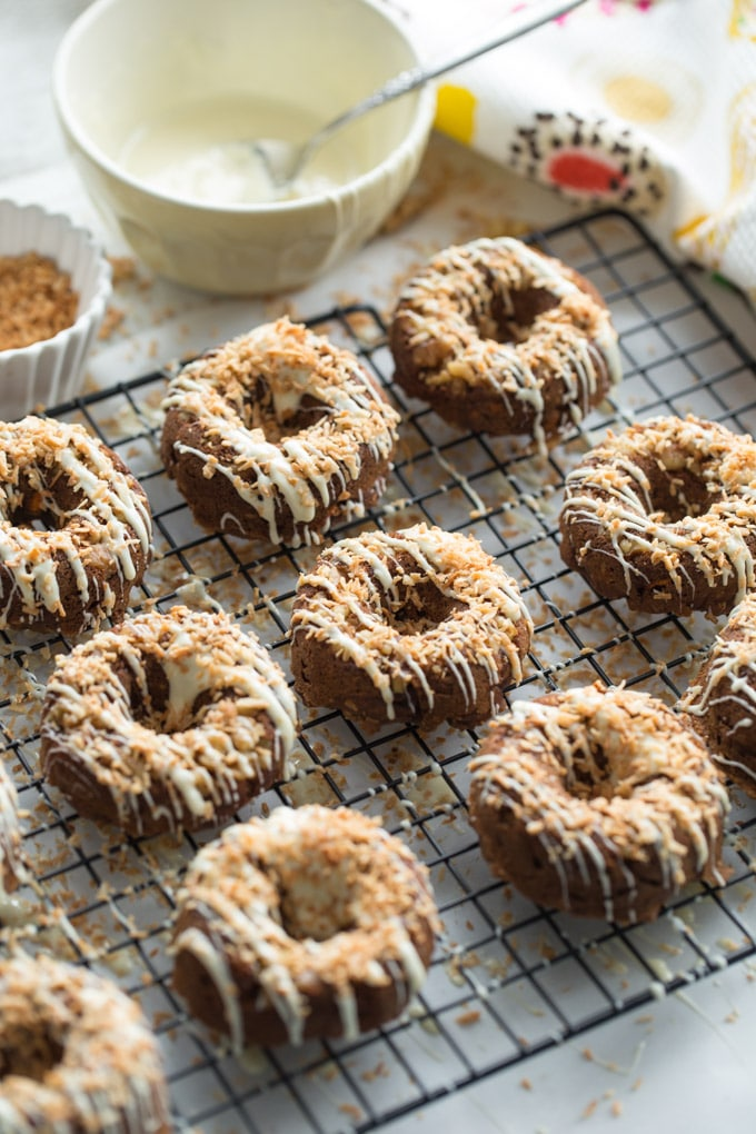 Coconut Carrot Cake Protein Donuts on a wire cooling rack with a bowl of white melted chocolate and toasted coconut in the background.