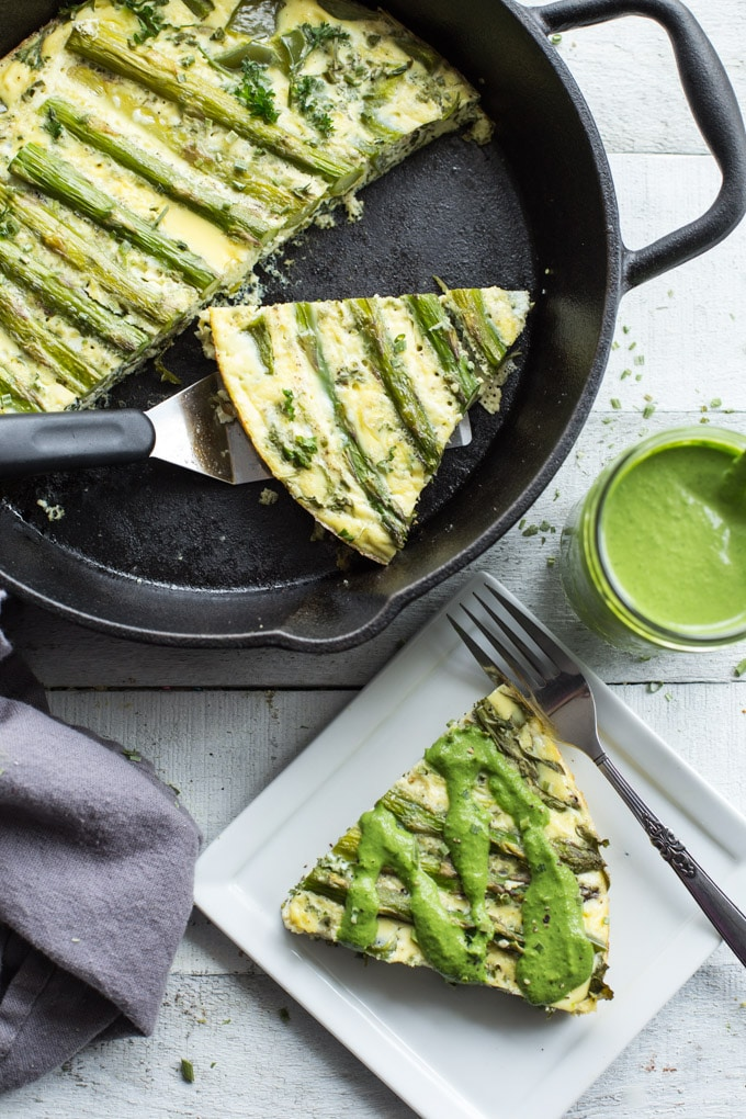 Overhead view of baked Green Goddess Crustless Quiche in a cast iron pan with a slice of quiche and a glass jar of jalapeño tahini dressing next to the pan.