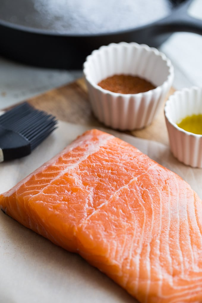 Raw salmon on a wooden cutting board next to spices and olive oil.