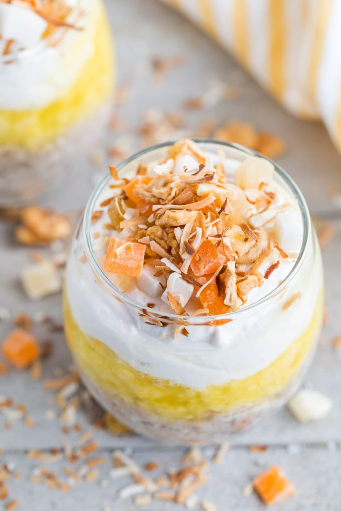 Pineapple Coconut Chia Pudding Parfait in a glass on a wooden surface.