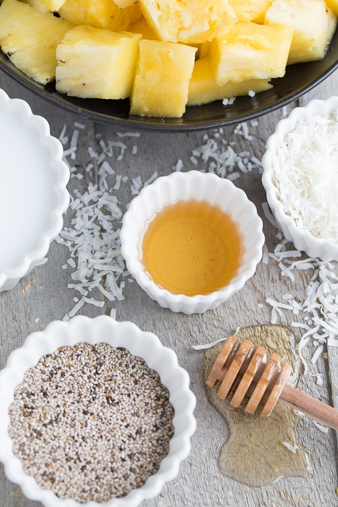 Ingredients for Pineapple Coconut Chia Pudding Parfait arranged on a wooden surface.