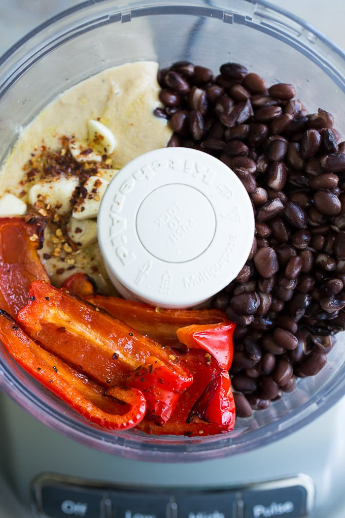 Overhead view of the ingredients for the Roasted Red Pepper and Black Bean Hummus in a food processor.