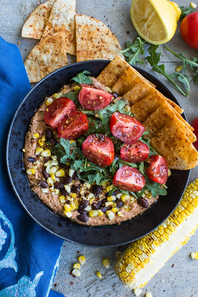 Overhead view of a Roasted Red Pepper and Black Bean Hummus Bowl on a wooden surface next to a blue napkin and other ingredients.