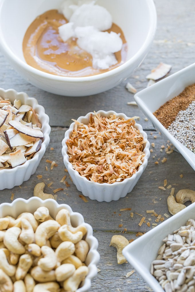 Overhead view of ingredients for Coconut Cashew Crunch Grain-Free Granola in individual dishes and spread out on a wooden surface.